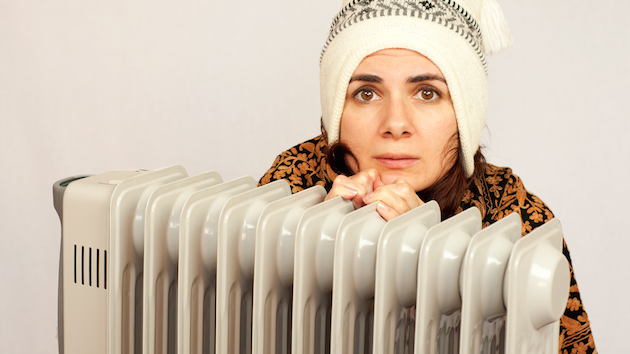 girl sitting in front of room heater